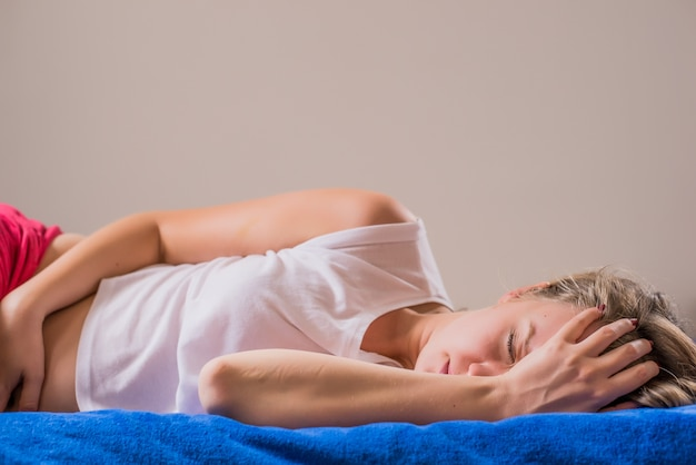 女性の痛み。腹部の痛みを感じる美しい女性の体の拡大写真。腹部に手を持って痛みを伴う胃酸に苦しんでいる体にフィットする少女。健康問題、ヘルスケアコンセプト。高解像度