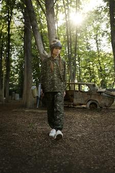 Пейнтболистка с ружьем позирует на детской площадке в лесу