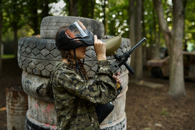 Female paintball player with gun poses on playground in the forest