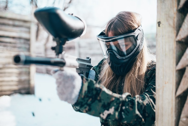 Female paintball player with marker gun in hands, winter forest battle. extreme sport game, woman fights in protection mask and uniform