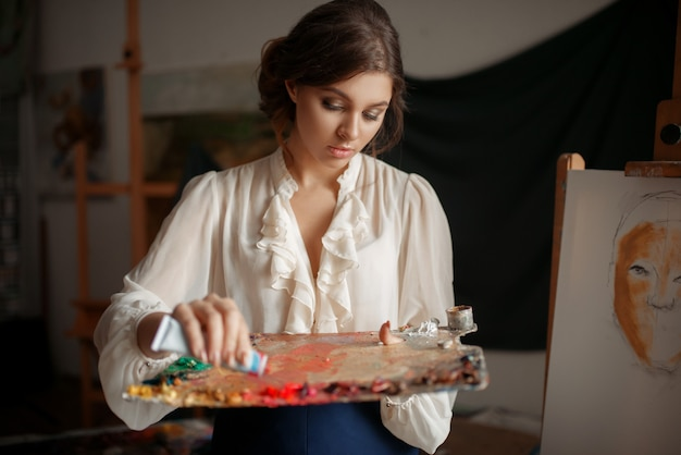 女性画家がスタジオでパレットに色を追加します。