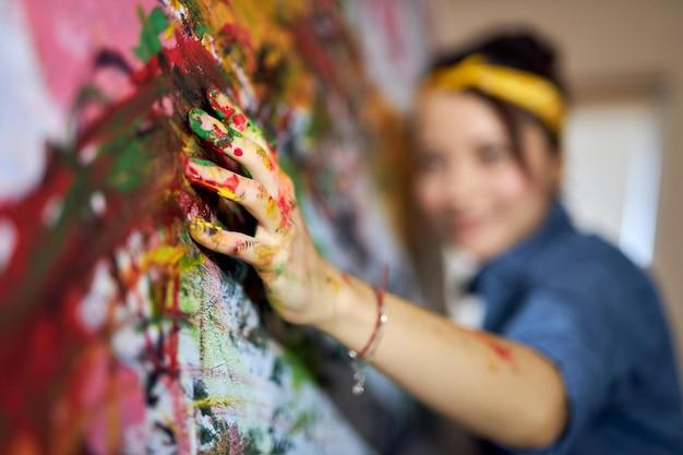 大きな現代の抽象的な油彩を作成しながら、指でキャンバスに絵の具を塗る女性画家
