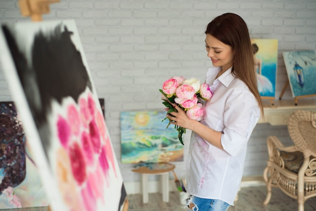 Female painter drawing in art studio using easel. portrait of a young woman painting with oil paints, side view portrait