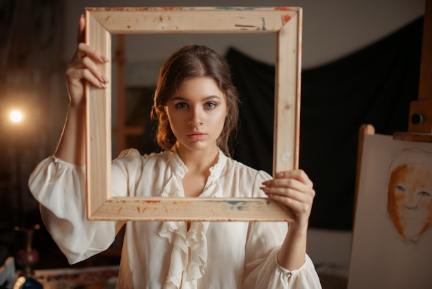 Female painter holds wooden frame at her face in studio