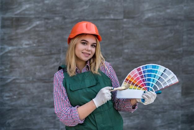 制服を着た女性画家とペイントチャート付きヘルメット。建設と建物のコンセプト