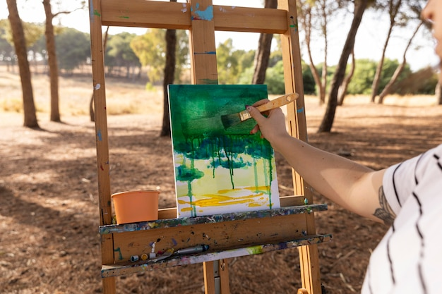 Female painter outdoors making landscape on canvas