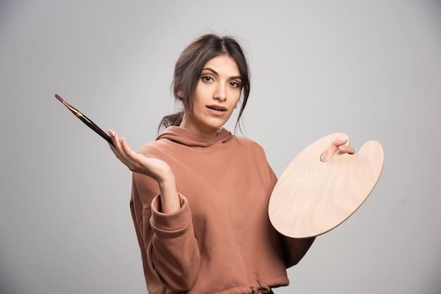 Pittore femminile che posa con la tavolozza e la spazzola vuote del pittore