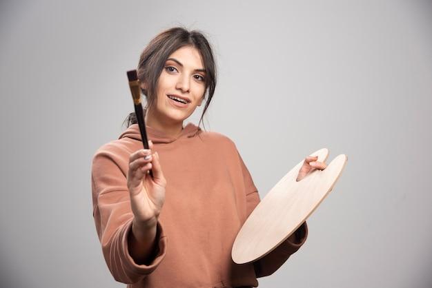 Pittore femminile che mostra il pennello su grigio Foto Gratuite