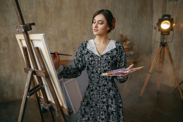 アートスタジオでブラシとパレットを描く女性画家。彼女の職場のアーティスト、ワークショップのイーゼルのクリエイティブマスター