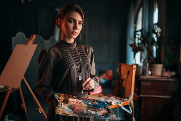 ブラシとアートスタジオでの手でパレットを持つ女性画家。油絵の具、絵筆画