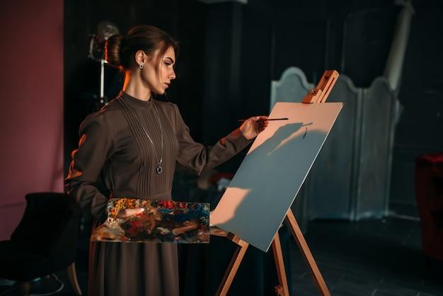 ブラシと手でパレットを持つ女性画家