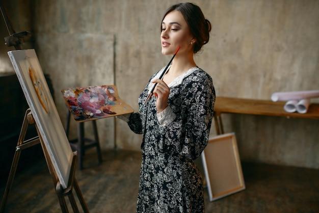 アートスタジオでブラシとパレットのポーズを持つ女性画家。彼女の職場のアーティスト、ワークショップのイーゼルのクリエイティブマスター