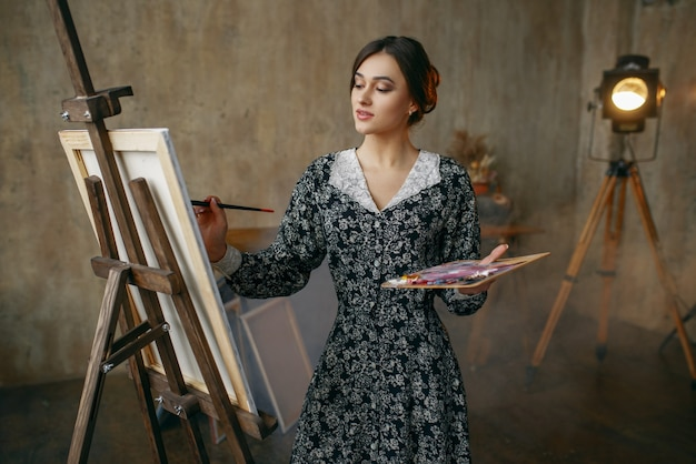 Female painter with brush and palette draws in art studio. artist at her workplace, creative master at the easel in workshop