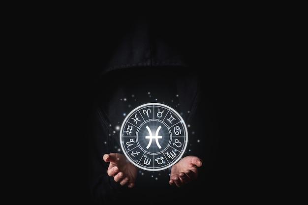 여성 손바닥에는 어둠 속에서 빛나는 조디악 표지판이 있습니다.