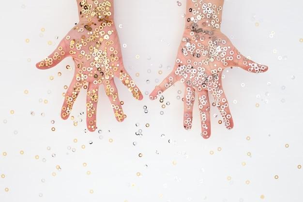 金と銀の紙吹雪の女性の手のひら