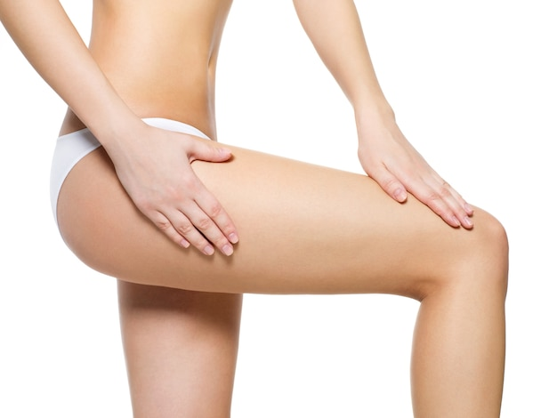 Female pampering cellulite skin on her legs - close-up shot on white space