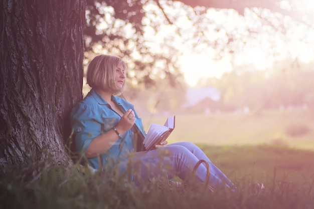 Female in the park on sunset with book