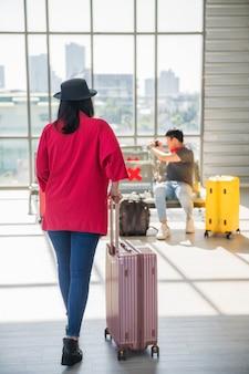 Пассажирка идет и тянет чемодан, чтобы сесть в зоне ожидания из-за задержки рейса или ждать вылета в терминале аэропорта. она идет к своим друзьям в зону ожидания.
