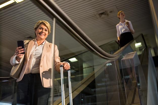Passeggera femminile che scende dalla scala mobile