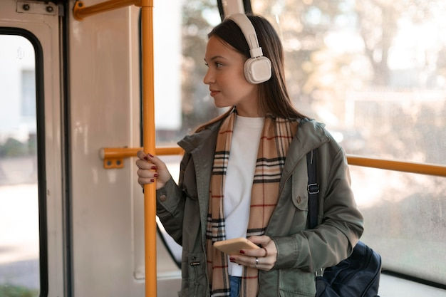 Passeggero femminile che tiene il palo del tram e distoglie lo sguardo