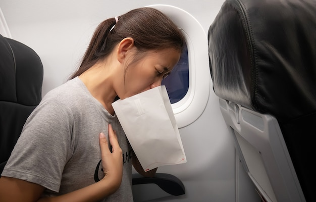 Female passenger on the plane felt airsick, affected with nausea due to travel in an aircraft using air sickness bag for vomiting due to airsickness