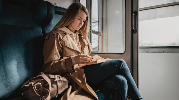 Female passenger reading in a train long view