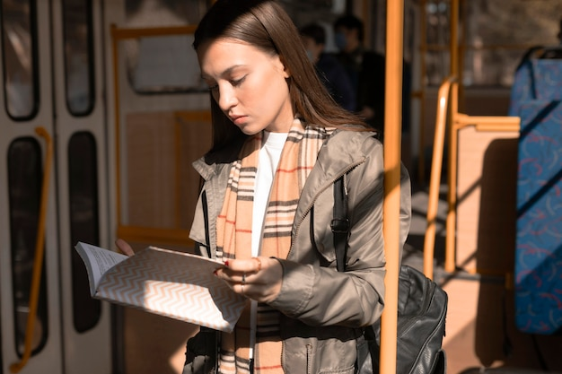 Female passenger reading and travelling by tram