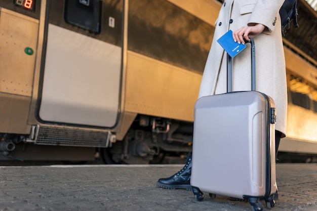 Female passenger with suitcase and passport at the railway station.