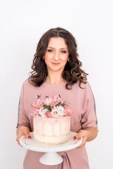 Female pastry chef holds a cake decorated with flowers on a white background