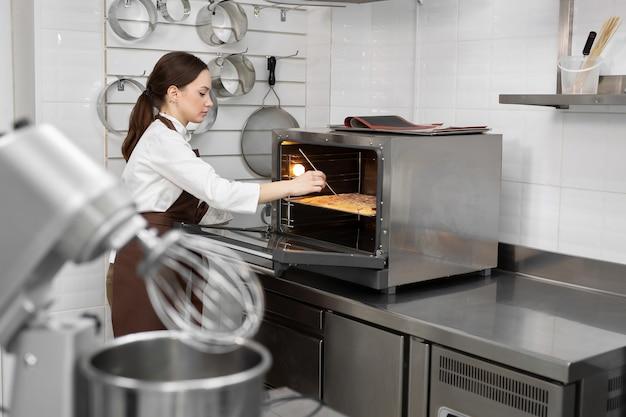 女性のパティシエがスポンジ生地をオーブンに入れ、木の棒で生地をチェックします