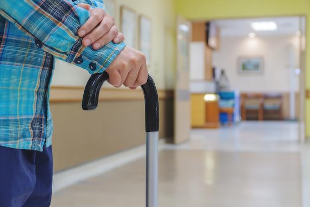 여성 환자는 병원에서 지팡이로 훈련하고 있습니다.