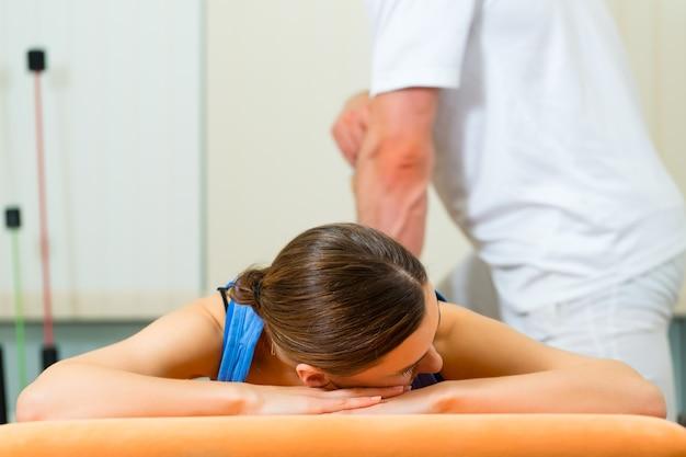 그녀의 치료사와 신체 운동을하는 물리 치료의 여성 환자, 그는 그녀에게 의료 마사지를 제공합니다