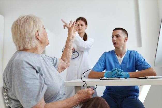 여성 환자는 병원에서 의사 및 간호사 조수와 의사 소통합니다.