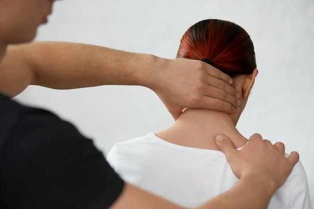 理学療法士と運動をしている女性患者。若い選手の負傷した首を治療する男性セラピスト。外傷後のリハビリ、スポーツ理学療法、回復の概念。
