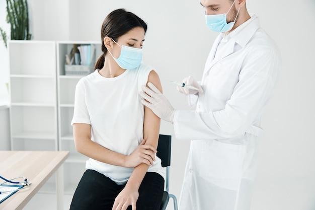 Пациентка получает вакцинацию covid19 в больнице и врач в медицинской маске