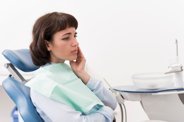 Female patient having a toothache at the dentist's office