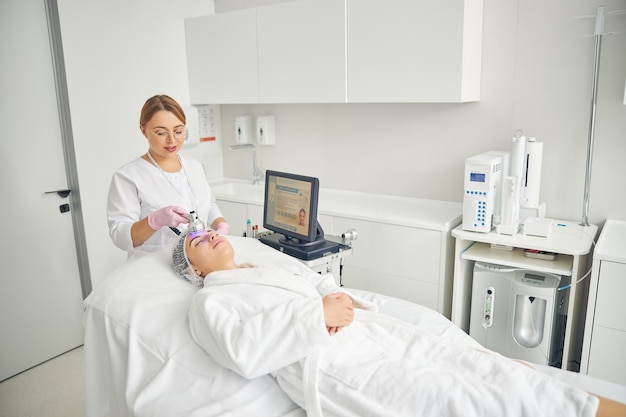 Пациентка в халате и марлевой шапочке на голове, проходящая терапию пурпурным светом