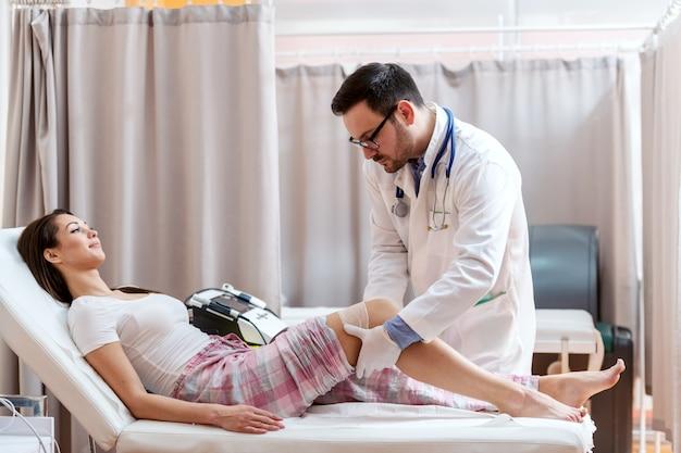 Женский пациент в пижамах лежа в больничной койке пока доктор в белой форме складывая ее поврежденное колено.