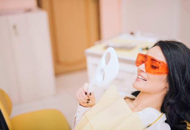 Female patient looking at mirror in dental office