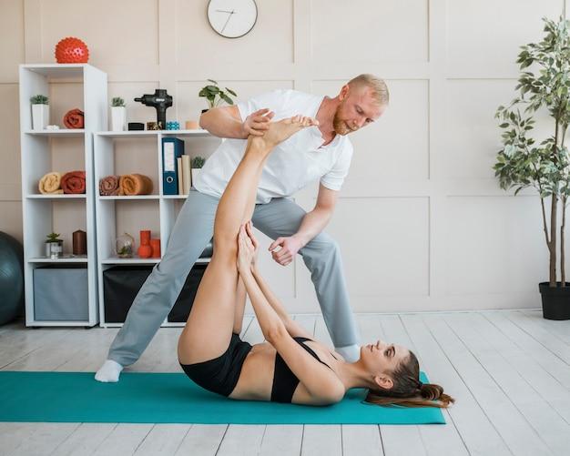 Paziente di sesso femminile in fisioterapia facendo esercizi con fisioterapista maschio
