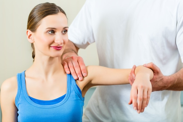 Female patient at the physiotherapy doing physical exercises with her therapist, he gives her a medical massage