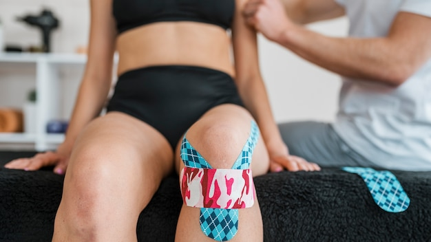 Female patient at physiotherapy with knee brace tape