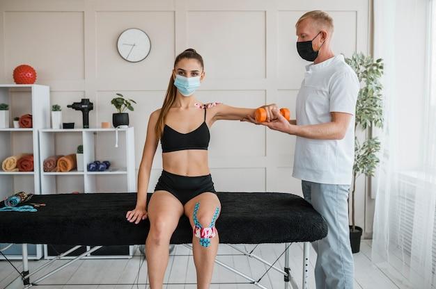 Paziente di sesso femminile in fisioterapia con uomo e manubri