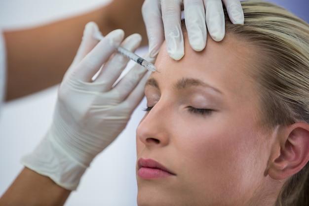 Пациентка, получающая инъекцию ботокса на лоб