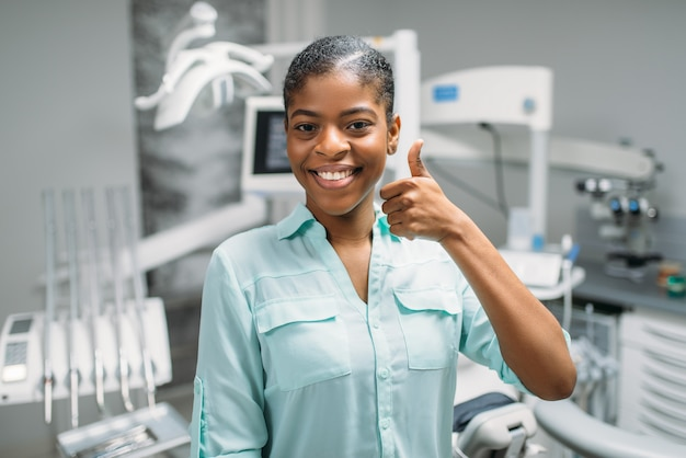 Female patient shows thumbs up in dental clinic