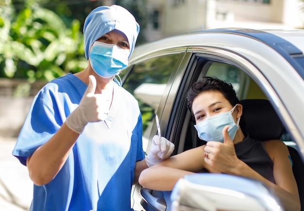 女性患者は車に座り、白人医師はフェイスマスクを着用し、covid 19注射針ワクチンスタンドを持ち、親指を立てて、ドライブスルーワクチン接種キューのカメラを見てください。