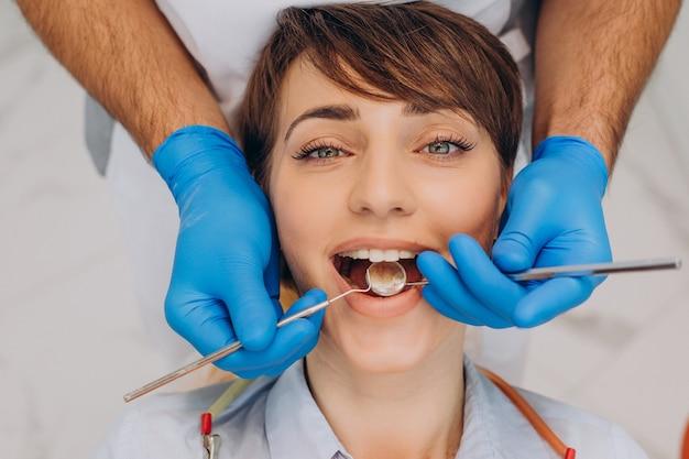 Paziente di sesso femminile seduto su una sedia da dentista e rendendo l'igiene professionale