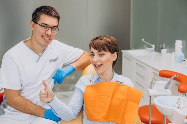 歯科医の椅子に座って専門家の衛生状態を作る女性患者