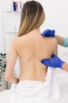 現代のリハビリセンターに座っている女性患者、女性理学療法士が腕を上げるのを手伝っている
