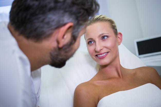 Женский пациент улыбается, глядя на доктора